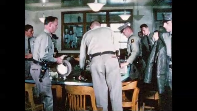 1960s: UNITED STATES: police officers sit in meeting. Officers start shift. Handover meeting at police station