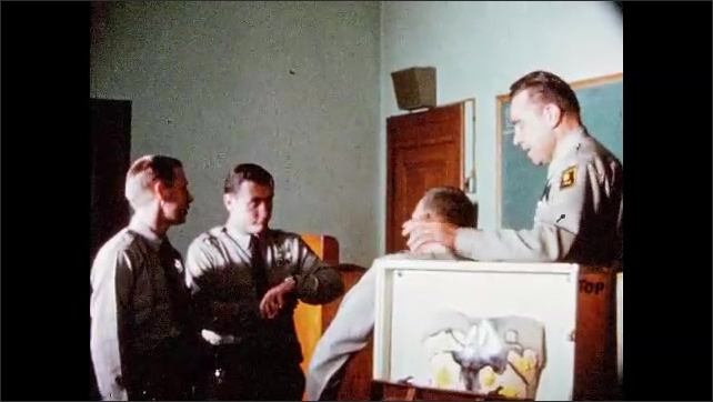 1960s: UNITED STATES: police student speaks to officer in academy training room.