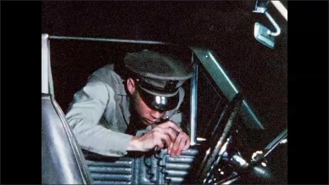 1960s: UNITED STATES: police man walks to patrol car at night. Officer speaks on radio in car.