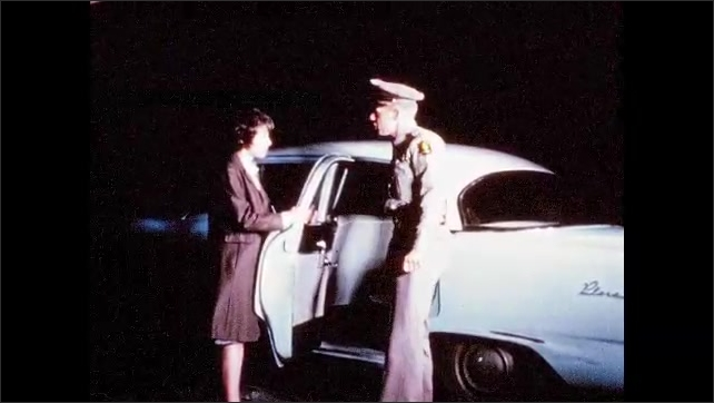 1960s: UNITED STATES: lady sits in car. Police man talks to lady by car. Police car in street at night