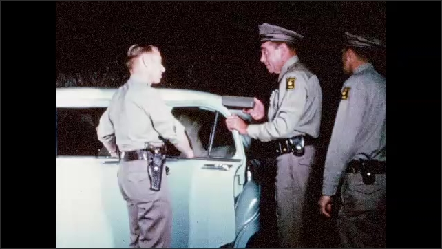 1960s: UNITED STATES: police officers talk by car door at night. Man gives tying tape to colleague. Lady gives birth in back of car.