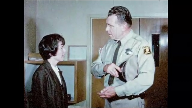 1960s: UNITED STATES: ambulance men wheel lady into hospital. Police man speaks to lady in hospital. Officer takes notes.