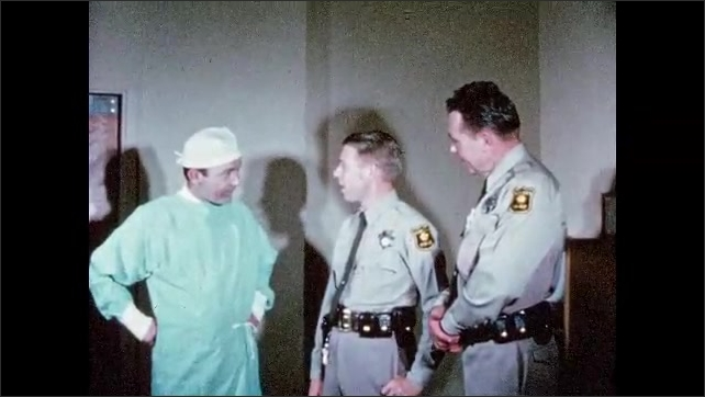 1960s: UNITED STATES: man and lady speak in hospital corridor. Police man talks to doctor.