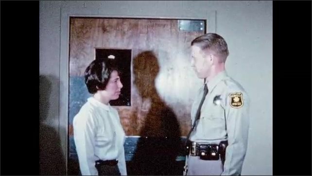1960s: UNITED STATES: police officer talks to lady in corridor. Lady speaks to officer. Lady shakes officer's hand.