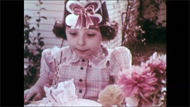 1950s: Group of girls wearing party hats sit around table, with woman, in backyard of home. Girl puffs into party favor then gets a piece of cake. Woman gives cake to other girl.