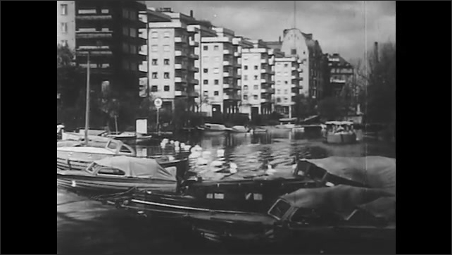 1950s: Canal surrounded by trees with Stockholm skyline in background. Boats are docked in marina with buildings in background.
