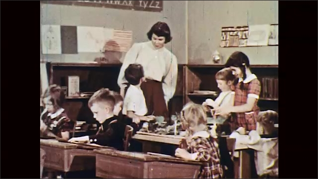1950s: boys and girls talk and build a cabin with Lincoln Logs and forest with leaves on table near student desks in classroom as woman chats and smiles near bookcase.