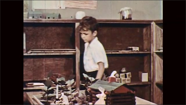 1950s: boys and girls place toys on cabinets and leave as boy places objects in cardboard box on shelf. boy yanks open desktop on student desk-chair, gets out paper, sits down and slams lid shut.