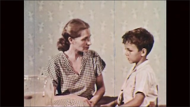 1950s: woman and boy embrace, sit on bed, look around bedroom and talk.