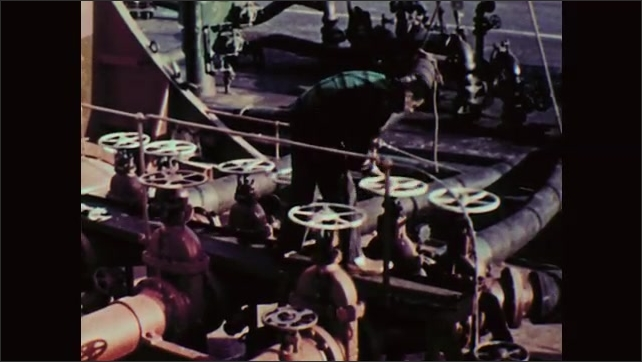 1950s: Men connecting hose to pipe. Man on ship opens valve. Hands turning valve. View of hoses connecting cargo ship and dock.