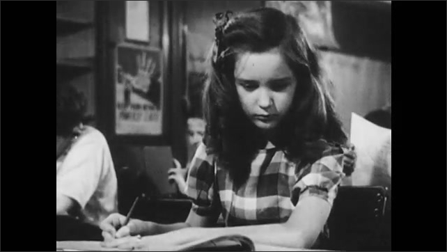 1950s: Teacher lectures and reads from her book at her desk. Students listen and take notes. Girl erases her answer and tries again. Boy taps girl on her shoulder to ask a question.