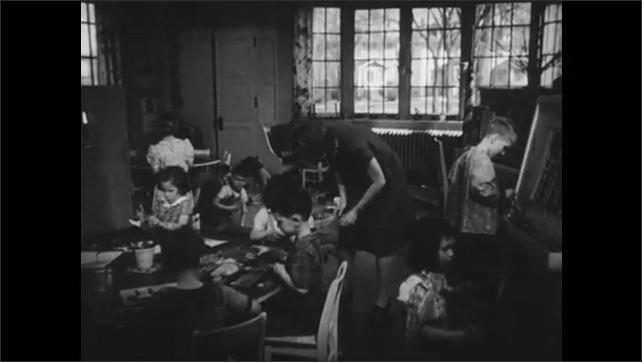 1950s: Teacher writes on the blackboard. Kindergarten teacher bends over students table to help. Teacher in front of class unfolds a paper.
