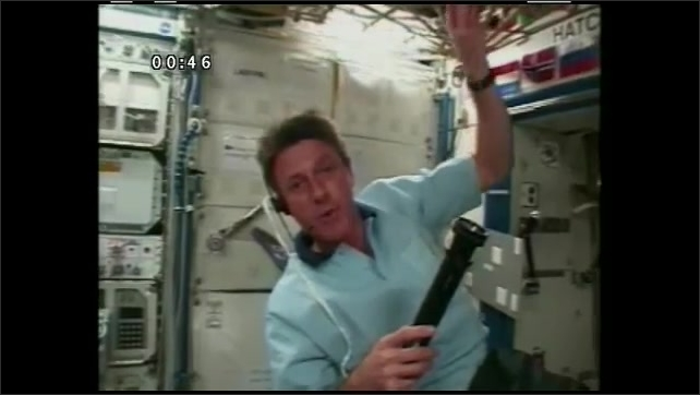 1990s: UNITED STATES: astronaut on ISS talks to camera. Astronaut holds flashlight. Flashlight in space.