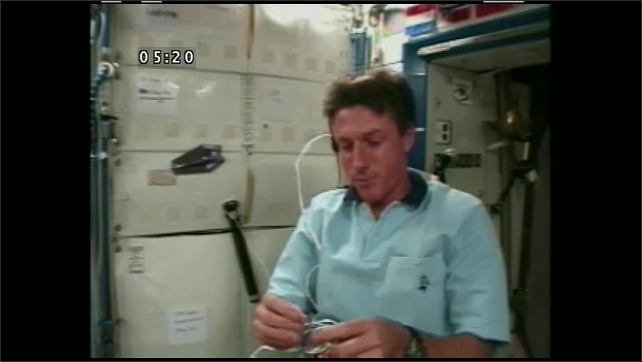 1990s: UNITED STATES: astronaut unties knot on gyroscope. String floats in space. Astronaut winds string around gyroscope rotor. Gimble attached to string.
