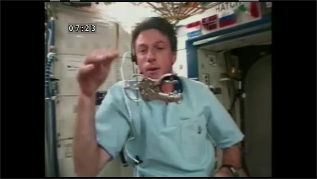 1990s: UNITED STATES: gyroscope rolls when pushed down. Gyroscope pushed upwards in opposite direction. ISS with heavy wheels.