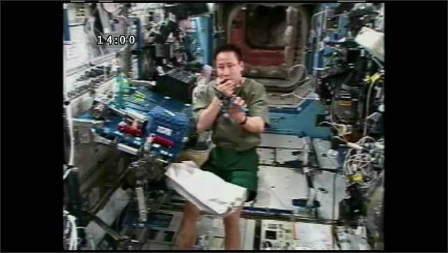 1990s: UNITED STATES: Astronaut puts microphone down and opens up packet. Astronaut shows sheers to camera. Tools for cutting metal.