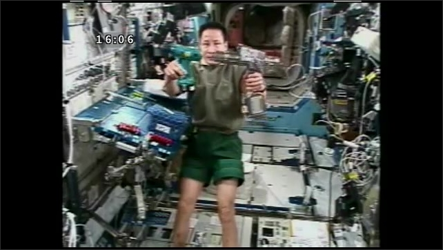 1990s: UNITED STATES: astronaut picks up drill from table on ISS. Drills side by side. Drills for inside and outside work on ISS.