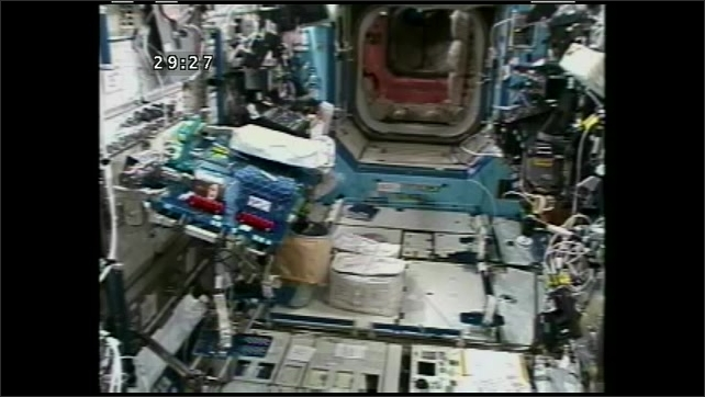 1990s: UNITED STATES: containers on floor near work bench on ISS. Equipment and switches anchored to walls of ISS.