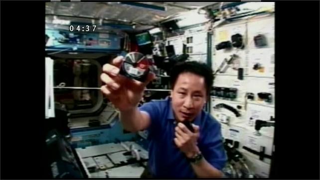 1990s: UNITED STATES: astronaut talks to camera,  Astronaut holds tape measure to camera. Tape measure retracts.