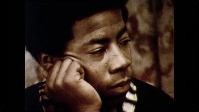 1970s: Men jog outside. Children play on baseball diamond. Men listen to man talk.