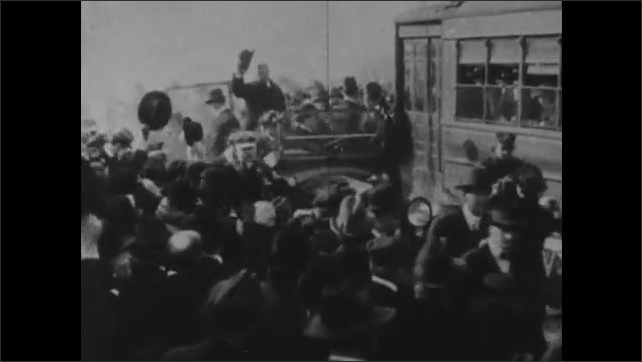1900s: Men climb into car surrounded by crowd of people. Cars parade down packed street as Theodore Roosevelt waves from car. The White House.
