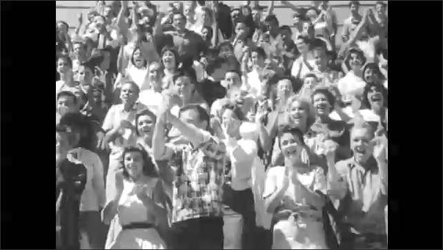 1960s: UNITED STATES: boys play in baseball match. Crowd cheer at baseball match. Lady claps. Reserves cheer at baseball match. Boys sit behind fence. Boy takes off baseball cap.