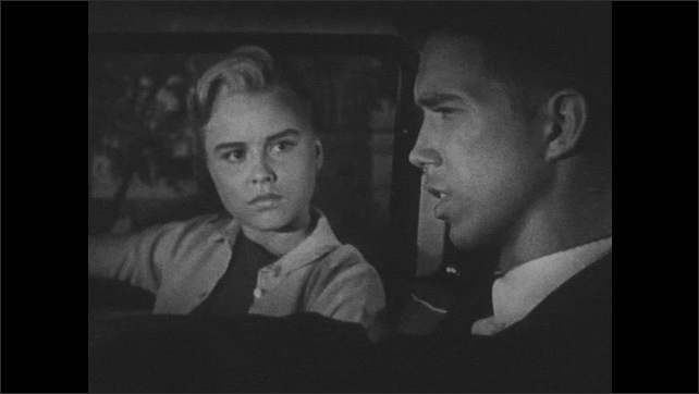 1960s: UNITED STATES: girl and boy speak inside front of car. Girl listens to boy. Boy looks worried.