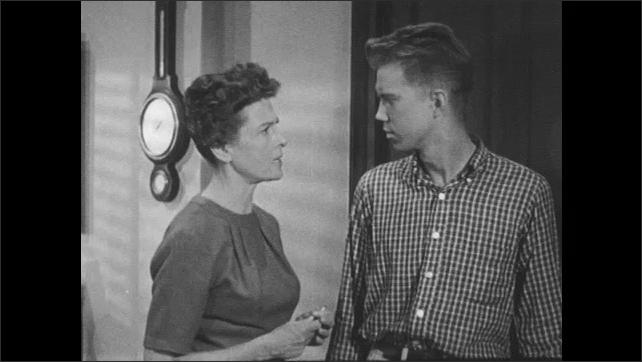 1960s: Boy reaches for door handle, woman walks over, talks to boy. Boy leaves office, woman looks upset.