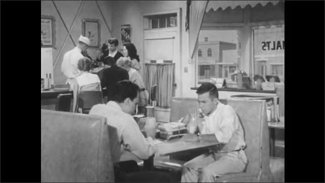1950s: Man speaks to family at dinner table. Man opens bible. Boys sit in booth at diner. Boys talk and drink milkshakes.