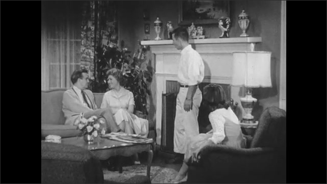 1950s: Family talks with each other in living room. Boy stands near fireplace.