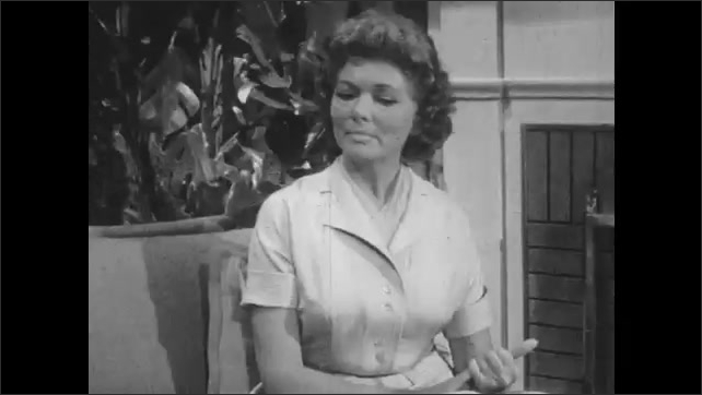 1950s: Woman sits on sofa and speaks. Man responds. Woman on sofa wrings hands and speaks.