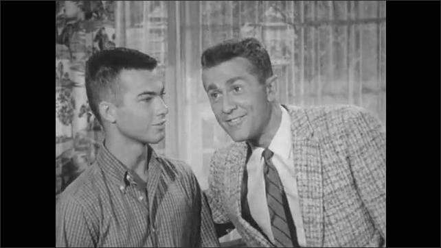 1950s: Woman talking toward camera. Two men standing, older man speaks toward camera, then both men walk out a door. The woman smiles.
