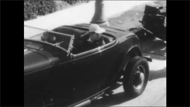 1950s: Car pulls to side of road, motorcycle stops behind car. Officer approaches car, talks to driver.