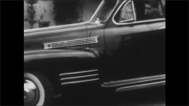 1950s: Panning shot, boy reversing car. Car runs over curb, backs into street. Tracking shot of car driving.