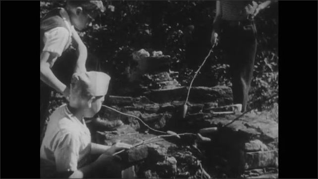 1940s: Kids gathered around fire at campsite, roasting hotdogs on sticks over fire.