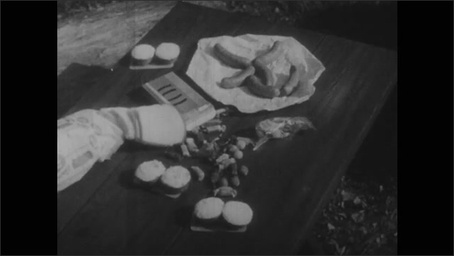 1940s: White breads, cheese, sausages and other foods lie on picnic table then disappear. Fruits, vegetable and bread appears on table.