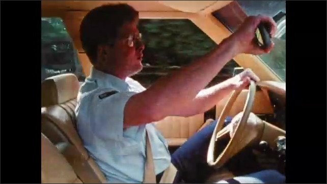 1980s: Car drives down palm tree lined street. Man drives car, sings and dances in seat. Man answers radio call in car.