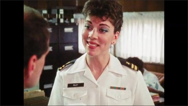 1980s: Man and woman in military uniforms stand and talk. Man behind couple eavesdrops, shakes head. Woman talks.