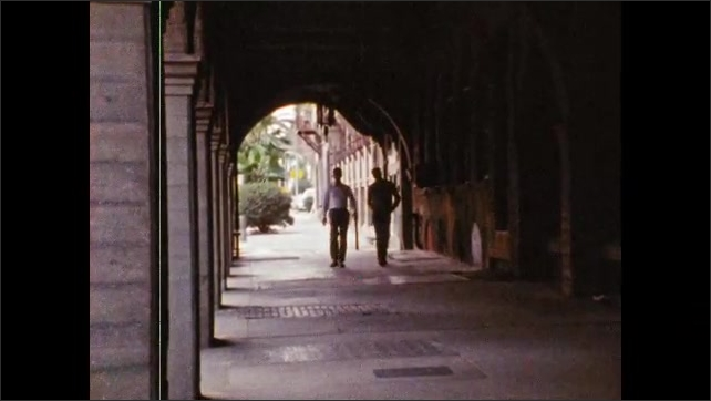 1980s: Two men walk down sidewalk, under arches. Military personnel work in office, woman talks, exits office.