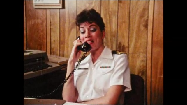 1980s: Woman in military uniform sits at desk in office, talks on phone.
