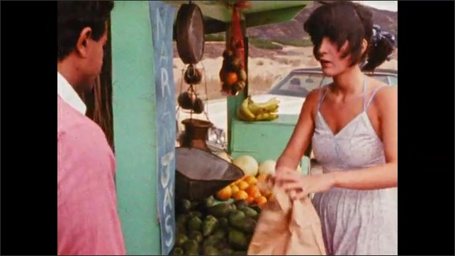 1980s: Car drives down road, pulls off next to roadside fruit stand. Woman bags up fruit, hands bag to man. Two men exit car, walk up to fruit stand, talk to woman.