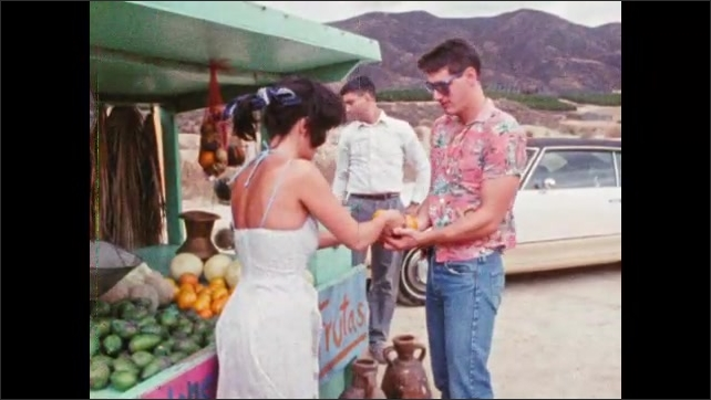 1980s: Two men stand at roadside fruit stand, man talks to woman, other man looks around. Woman hands man oranges, man hands woman money, men walk away, woman turns back towards display.