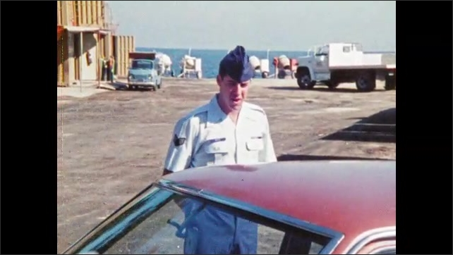 1980s: Two men in military uniforms walk across base, stop at car. Men stand next to car, talk. Man walks around car, inspects it, other man follows.