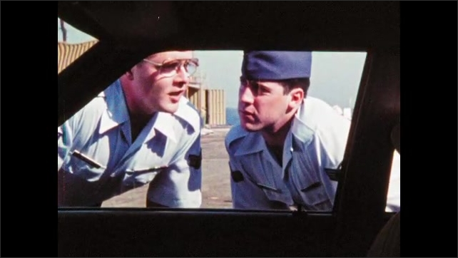 1980s: Two men in military uniforms inspect car. Man jiggles gas cap, closes gas door. Men look through car window, talk. Man drops to ground, other man follows.