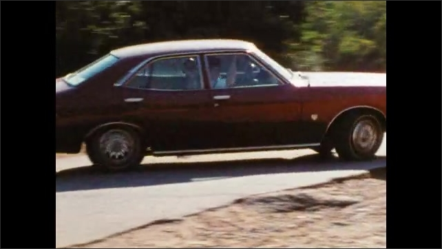 1980s: Two men in military uniforms ride in car, talk. Man brakes, reverses car, turns car around quickly, drives away. Car weaves through palm trees.
