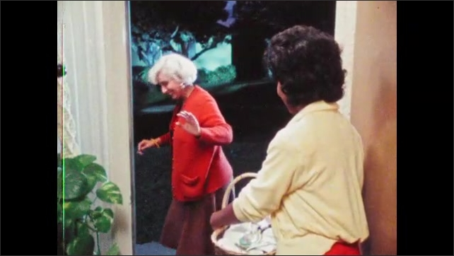 1980s: Two women stand in doorway, talk. Woman hands woman lollipop, women say goodbye, woman closes and locks door.