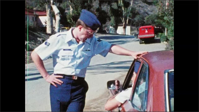 1980s: Man in military uniform stands next to car, hands keys to man in driver's seat, talks. Man pats hood of car, car drives away.