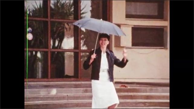 1980s: Woman in military uniform walks down steps, opens umbrella, waves at passing cars.