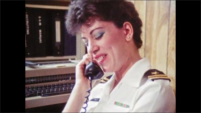 1980s: Woman in military uniform sits in office, talks on phone, laughs, smiles. Woman exits building, walks down steps.