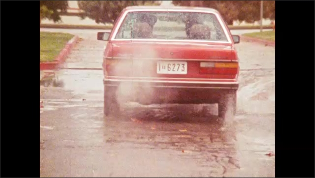 1980s: Woman in uniform walks around red car, gets in passenger side, kisses man inside. Car drives away. Man drives car. Man puts glasses on, looks around.